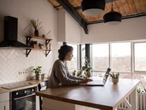 Imagem de uma mulher em casa usando o computador para aprender como resgatar previdência privada