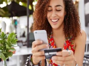 mulher com celular e cartão, representando banco digital indeniza cliente