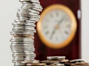 pilha de moedas com um relógio ao fundo desfocado representando corte de juros