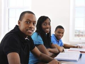 Três univesitários negros sentados na carteira e sorrindo, representando Desafio Unilever