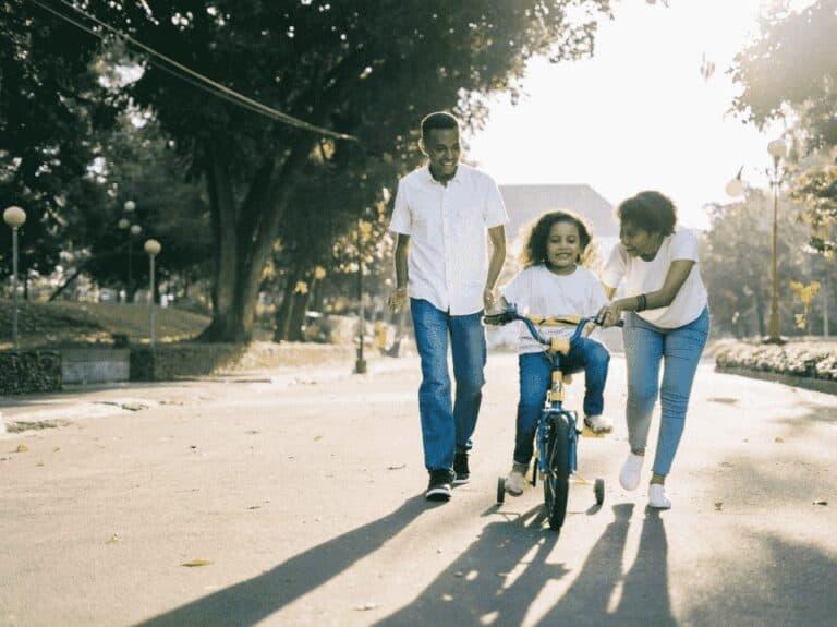 pais com criança em bicicleta, representando descontos no dia das crianças
