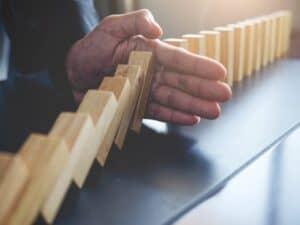mão parando dominó, representando dinheiro em renda fixa está à perigo com a taxa Selic baixa