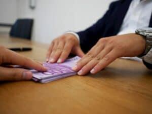 Close em mãos passando dinheiro de uma pessoa para outra representando empréstimos do INSS em banco digital