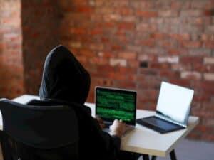 hacker em notebook representando fraude financeira