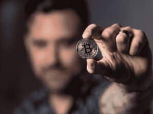 homem segurando bitcoin, representando fundo 100% em bitcoin