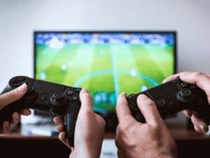 dois controles de videogame em frente a TV, representando fundo com foco em games