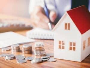 casa em miniatura e moedas, representando gasto excessivo com aluguel