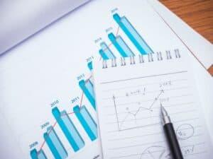 papéis com gráficos e caneta em cima de bloco representando inflação de aluguel