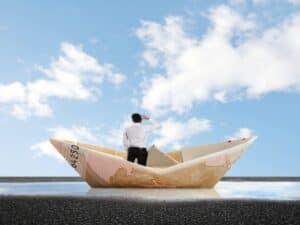pessoa em barco de papel, representando Investidores estão deixando o Brasil a procura de economias mais sólidas para seus investimentos