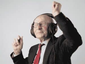 idoso com fones de ouvido dançando, representando investir em música