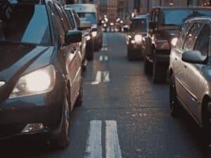 carros enfileirados em rua, representando lei que altera código de trânsito