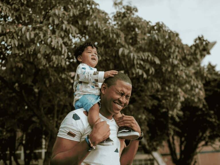 homem com criança nos ombros, representando mês das crianças inter