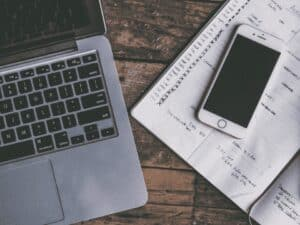 computador, celular e papel, representando negociação de dívidas com desconto