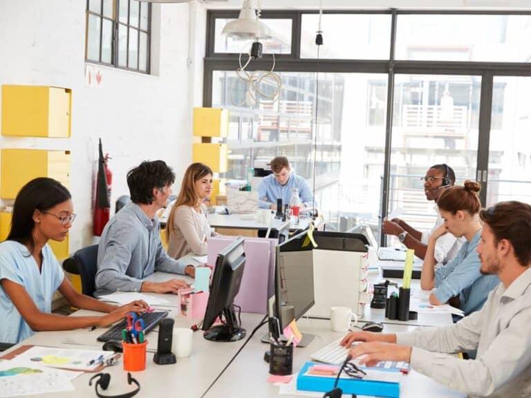 7 funcionários trabalhando em seus respectivos postos de trabalho, representando oportunidades de trabalho para jovens vulneráveis