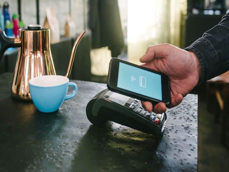 celular e maquininha de cartão, representando pagamentos em débito nos aplicativos
