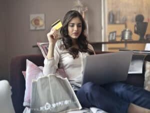 mulher com computador e cartão de crédito, representando produtos na black friday