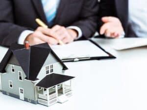 Maquete de casa com pessoas negociando ao fundo, representando portabilidade de financiamento imobiliário