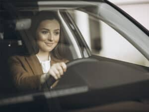 Imagem de uma mulher dirigindo um carro e sorrindo, representando o conteúdo sobre proteção veicular