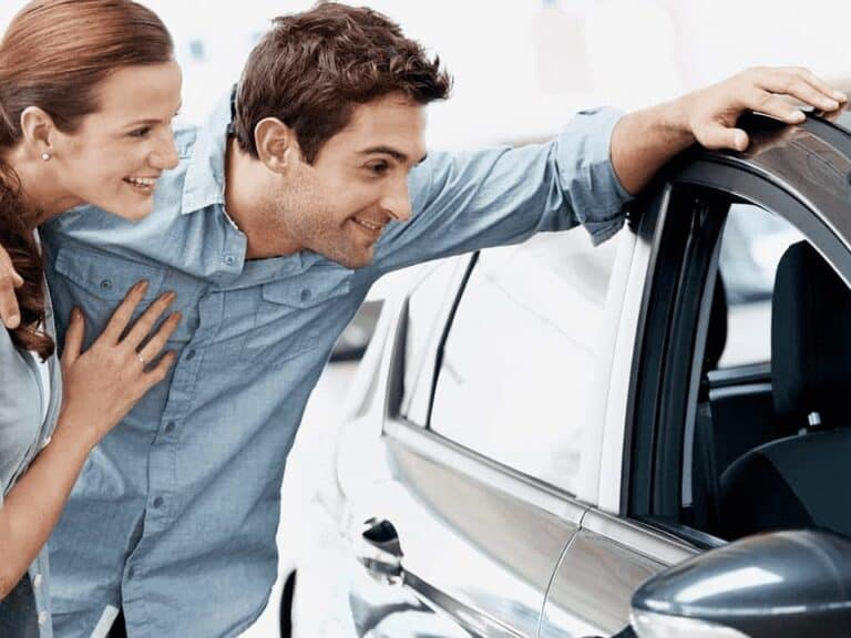 casal olhando carro novo, representando refinanciamento de veículo Santander