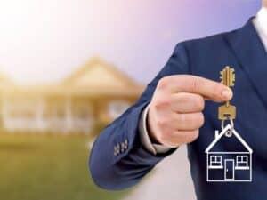 Homem segurando chave com uma casa ao fundo, representando seguro fiança