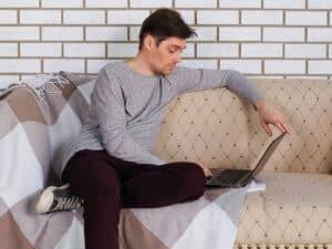 simulador habitacional santander ilustrado com um rapaz assentado no sofá, mexendo no notebook