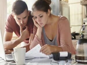 casal desanimado confere papel em frente a computador representando taxa de desemprego no Brasil bate recorde