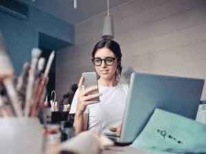 mulher no celular, representando taxa para transferência do auxílio