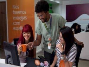 funcionários conversam diante de computador representando vagas para desenvolvedores de software