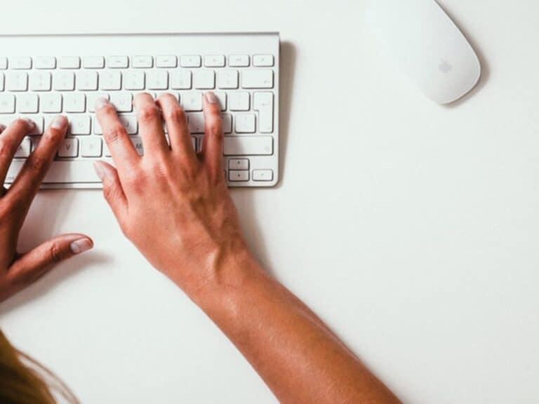 Pessoa digitando em teclado, representando 100 vagas de emprego abertas