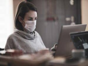 mulher de máscara acessando notebook representando 13º salário de quem teve contrato suspenso ou salário reduzido