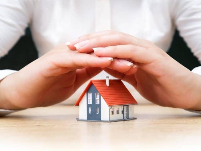 mãos segurando casa em miniatura, representando imóveis com desconto na black friday