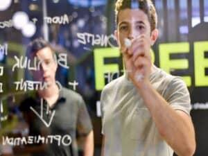 jovem escreve em quadro transparente representando Programa de aceleração de startups do Boticário