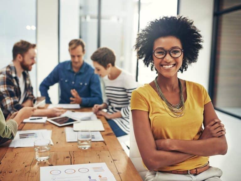 Profissional em primeiro plano sorrindo enquanto os demais profissionais ou fundo conversam em mesa de reunião, representando Programa de trainee Comgás