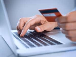 pessoa no notebook com cartão, representando pagamentos online