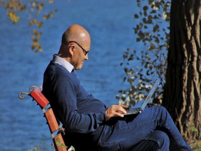 homem acessando notebook sentado em banco de praça representando Tábua IBGE-201