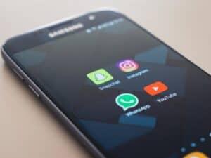 Tela de smartphone com ícones de aplicativos, incluindo o WhatsApp, representando Versões alternativas do WhatsApp