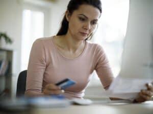 Mulher com cartão de crédito e boleto nas mãos, representando App para pagar boleto com cartão de crédito