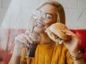 mulher bebendo refrigerante e comendo hamburguer, representando black friday das redes de fast-food