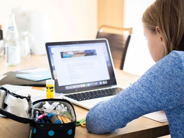 menina de costas olhando para uma tela de computador para estudar com materiais de escola ao seu lado, como cola, lápis, estojo e mais