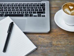 notebook, caderno, caneta e xícara de café representando curso gratuito para carreira em tecnologia