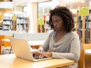 mulher sentada em frente ao computador digitando e sentada em uma biblioteca estudando