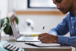 homem de camisa social sentado em frente ao computador estudando e fazendo anotações em um caderno