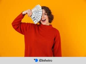 mulher segurando notas de dinheiro representando o décimo terceiro salário