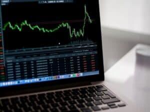 notebook com mercado de ações na tela representando desistências de IPOs