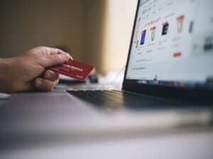 pessoa com cartão de crédito e computador, representando aumento do limite do cartão