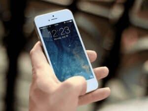 mão segurando celular, representando empréstimo com garantia de celular