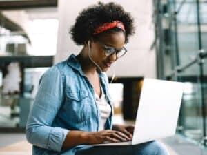 mulher jovem utilizando computador, representando estágio na bolsa de valores