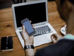 homem com computador e celular, representando fase restrita do PIX