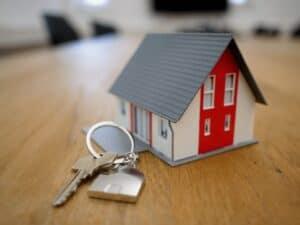 maquete de casa ao lado de uma chave com chaveiro de casa, representando financiar um imóvel