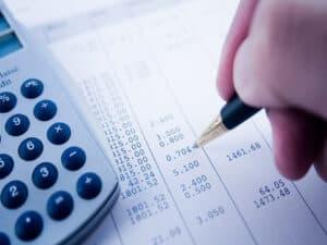 calculadora e conta, representando pagamento de imposto e taxa de passaporte
